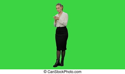 Annoyed young woman having bad news from her angry boss by the phone on a Green Screen, Chroma Key.