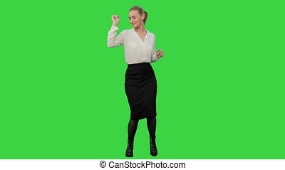 Businesswoman dancing wildly celebrating successful project on a Green Screen, Chroma Key.