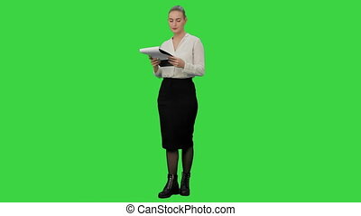 Young businesswoman reading documents aprroving the result on a Green Screen, Chroma Key.