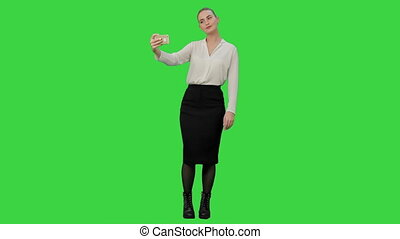 Young pretty businesswoman take selfie with cell phone on a Green Screen, Chroma Key.