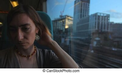 Middle aged woman sitting near the window in the train, looking and thinking about her life.