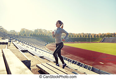 happy young woman running upstairs on stadium - fitness,...