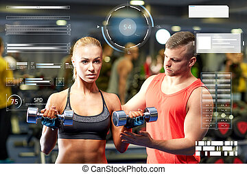 young couple with dumbbells flexing muscles in gym -...