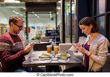 happy couple with smartphones at vegan restaurant -...