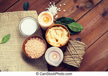 close up of natural body scrub and candles on wood - beauty,...