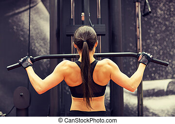 woman flexing muscles on cable machine in gym - sport,...