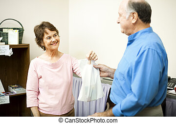 Thanks For Your Business - Friendly store clerk hands a...