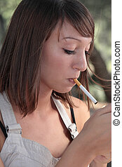 Portrait of a pretty young woman lighting a cigarette...