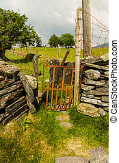 Old iron gate stile in dry stone wall