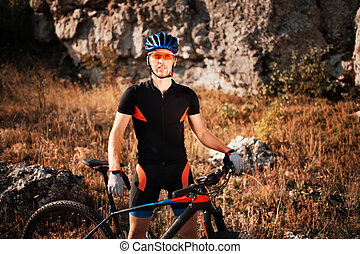 Portrait of a cyclist in helmet and sunglasses on a mountain bike. Active sport in nature.
