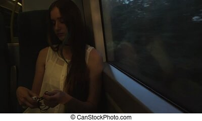Young brunette beautiful hipster girl with long hair unravels the headphones, sitting by the window in the train.
