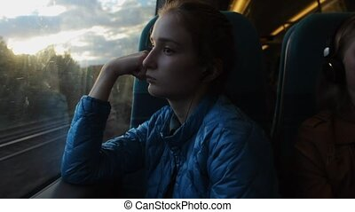 Young brunette beautiful hipster girl looking to the window in the train and thinking about her future.