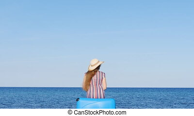 Traveler woman sitting on her suitcase on the beach -...