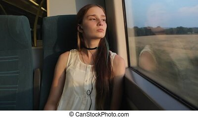 Young brunette beautiful hipster girl with long thinking about her life, sitting by the window in the train.