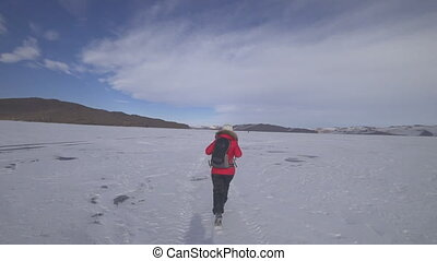 The tourist runs on the ice of the lake.