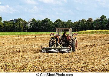 Tractor with plough doing agricultural seasonal work at...
