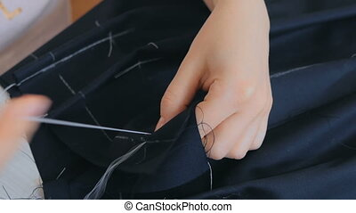 Close up shot. Professional tailor, fashion designer working...