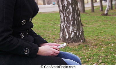 Young Girl using a Mobile Phone on a Bench in the City Park