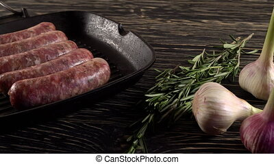 Raw sausages with garlic, rosemary on wooden surface - Raw...