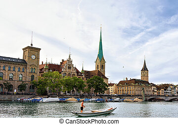 Man Fraumunster Church and St Peter and boats Limmat Zurich...