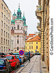 Street with St Nicholas Church in Lesser Town Square Prague...