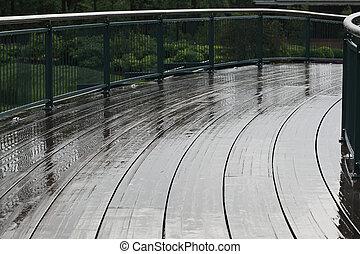 Curved Boardwalk - Wet boardwalk bridge curves across...