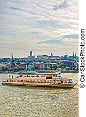 Ferry at Danube River and Buda city embankment in Budapest,...