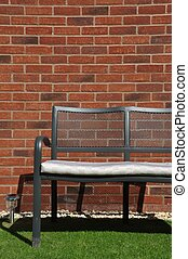 Garden bench - outdoor bench at a grass garden (brick wall...