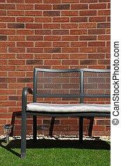 Garden bench - outdoor bench at a grass garden (brick wall...