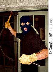 Aburglar robbing a house wearing a balaclava.