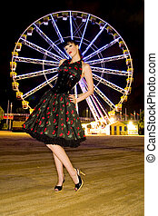 A beautiful pin up model posing infront of a ferriswheel at...