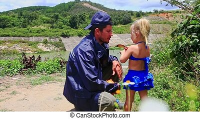 Close Father Squats Little Girl Takes off his Cap on River...