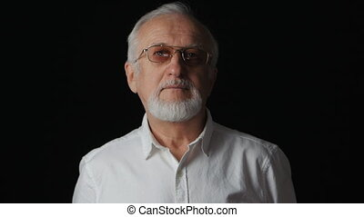 Close up portrait of senior man in a white shirt on black background