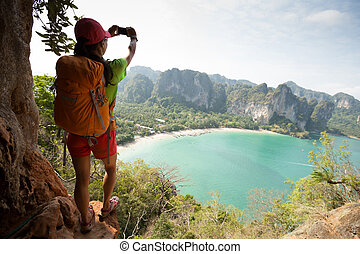 young woman hiker taking photo on seaside mountain cliff