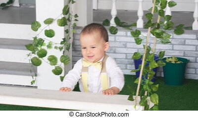 Boy in white shirt and suspenders from a swing