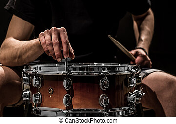 man adjusts a percussion instrument, musical concept with the working drum