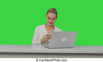 Happy woman is dancing on her own using smartphone at work place on a Green Screen, Chroma Key.