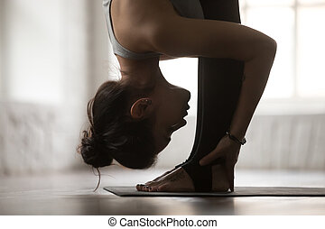 Young woman in head to knees exercise, white studio, closeup...