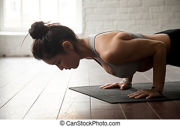 Young attractive woman in chaturanga dandasana pose, loft...