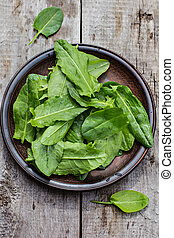 sorrel leaves on a plate, the plate is on the old boards