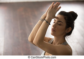 Young attractive woman making namaste with closed eyes,...