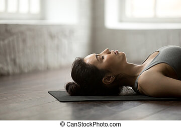 Young attractive woman lying in Corpse pose, white loft...