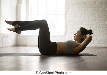 Young attractive sporty woman practicing Sit Ups exercise,...