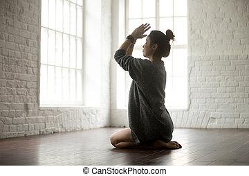 Young attractive woman in vajrasana pose, white loft studio...