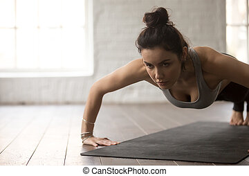 Young attractive woman in chaturanga dandasana pose, white...