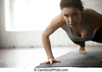 Young attractive fitness woman practicing Push ups - Young...
