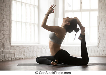 Young woman in One Legged King Pigeon pose, white studio -...