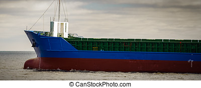 Blue cargo ship's bow leaving the port of Riga
