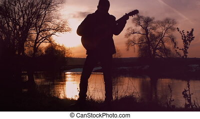 The man playing the guitar at sunset (silhouette)