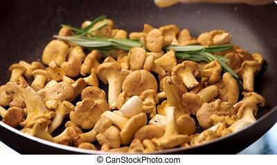 Chanterelles in a pan. Mushrooms with garlic and rosemary.